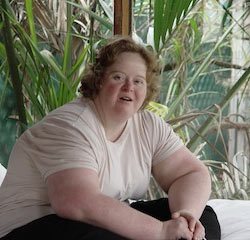 A young woman with a learning disability smiles at us. She is seated in a Summer house surrounded by lush vegetation.