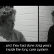 Black and white screenshot from the documentary 'Voices from the Knitting Circle', produced in 2018. Split screen, a blonde woman with short hair on the left (Rachel High) interviewing a woman with short blonde hair on the right (Julie McNamara). Subtitles on screen read :...and they had done long years inside the long care system'.