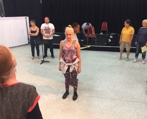The back of a woman on the left hand-side corner of the photo; she looks towards the centre of the photo, where six people stand in pairs and create a triangle in the space. Another person in the background is on a small stage, pushing a theatre chair.