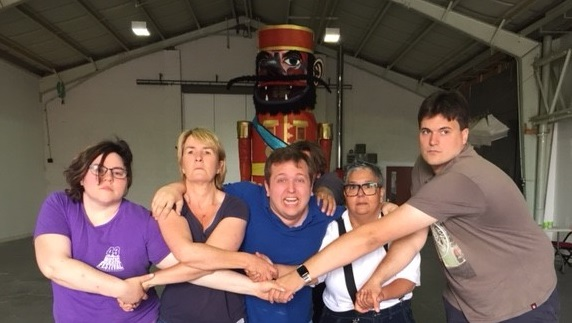 Group photo from Pullen's Party Creative Lab in June 2018. Six actors-participants are marching towards the viewer, holding each other's hands in solidarity and with determination. Behind them, the replica of Pullen's giant puppet.
