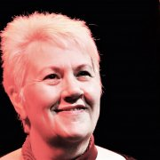 Vici is a white woman in her fifties with blond spiky hair. A portrait photograph, she is standing on a stage looking upwards smiling.