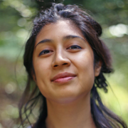 Nicole, an Indo-Guyanese woman with a half bun smiles at the camera.