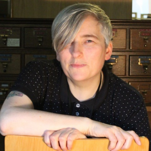 Profile photo of a white woman with short grey hair with a fringe on the left. She is in a room with office drawers behind her and she is smiling.